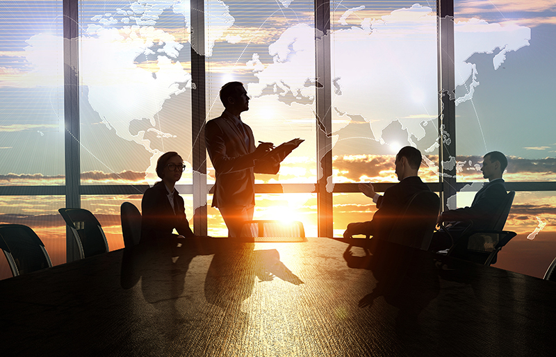 Business people silhouetted against a window, at a boardroom table, with a map of the world ghosted in background