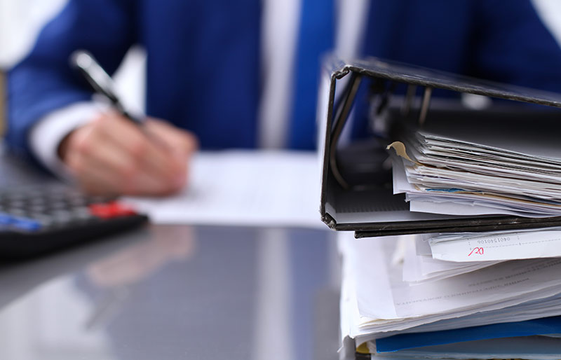 An image focusing on binders at the front with a businessman working in a blurred background with a pen and calculator .
