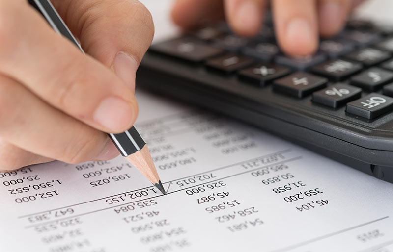A close- up of a hand checking a financial statement using calculator and pencil.