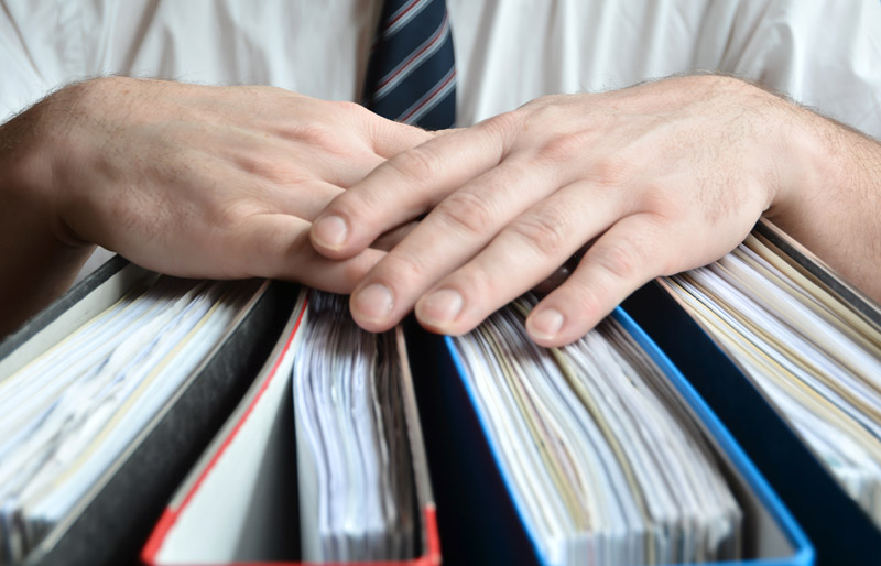A close-up image of a males hands holding numerous binders.