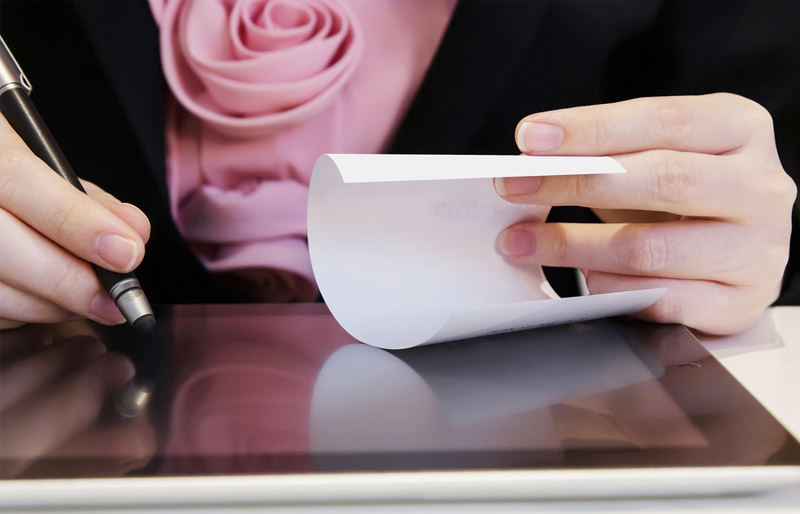 Business woman checking receipt against data on tablet