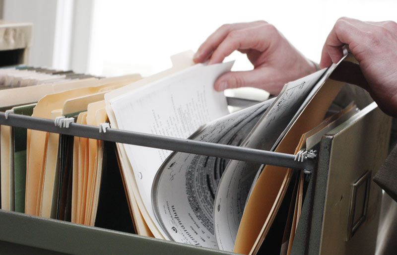 Businessman sifting through documents in file folder in filing cabinet
