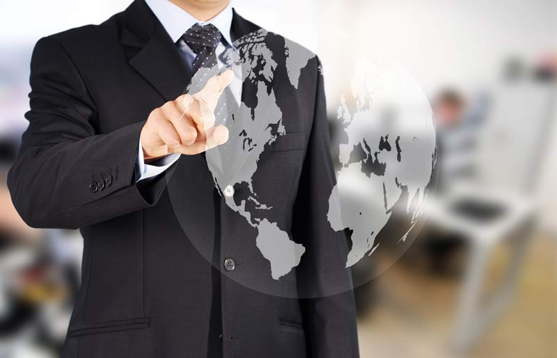 Accounting Professional pointing to a world map on a glass screen.