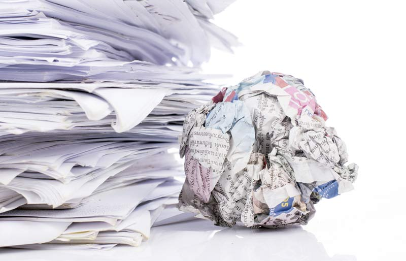 A stack of tax forms with a ball of crumpled up paper.