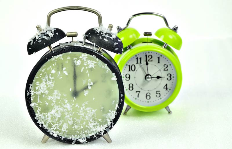 An image close-up of two alarm clocks one black and one green with the black one covered in ice and snow crystals.