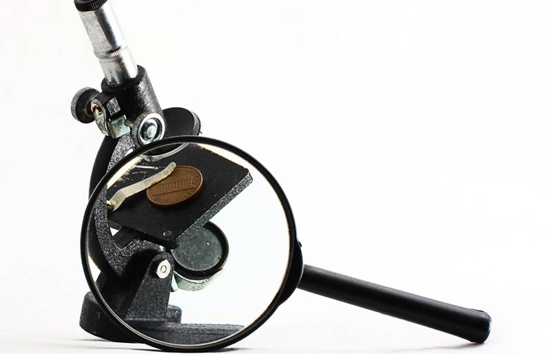 An close up image of a Microscope with a Penny on the viewing platform and a magnifying glass.