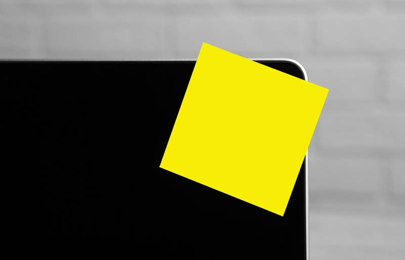 A close-up photo of a laptop screen with a yellow post-it note attached on the corner.