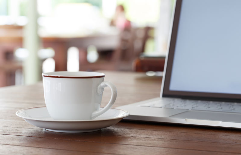 A close-up image of a laptop and a coffee cup sitting on a desk.