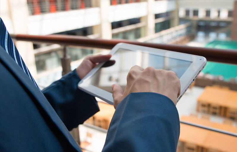 A close-up of a business professional checking an update on his tablet PC as he looks out over a warehouse.