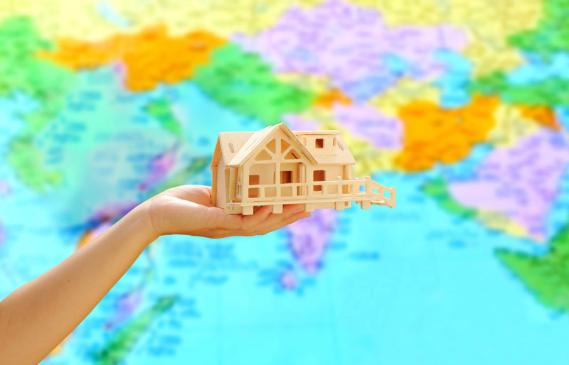 A close-up of a female holding a model of a house in her palm with a world map in the background.
