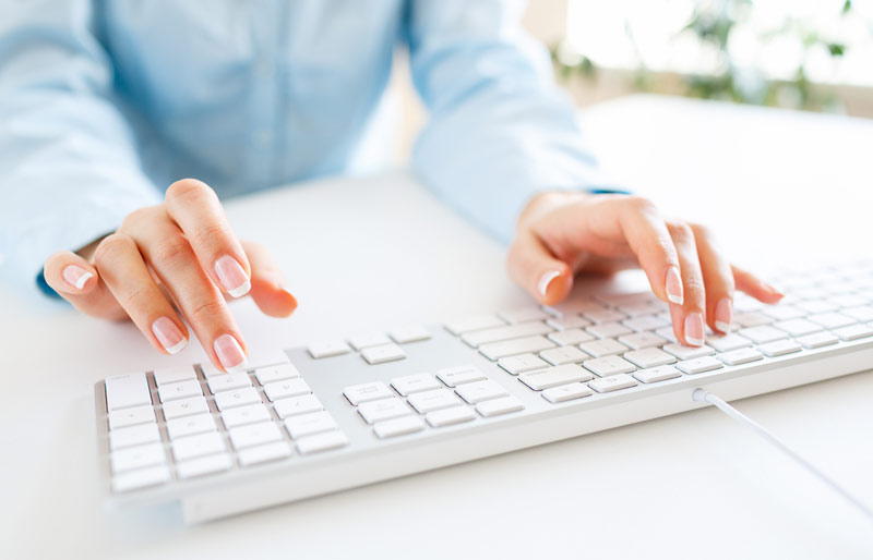 A croped photo showing a female business professional typing on a keyboard.