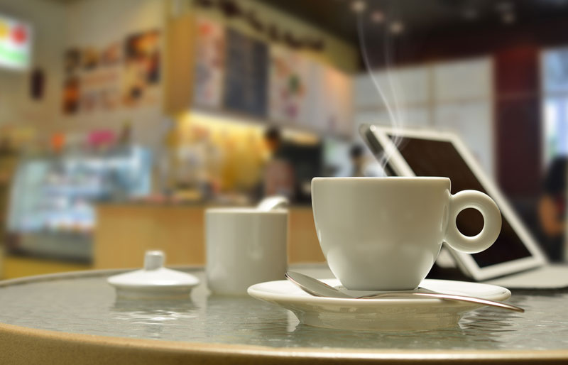 A photograph of a coffee shop table with a coffee, tablet PC and sugar bowl.