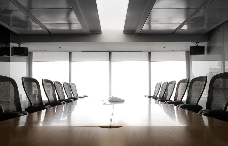 A wide angle image of the inside of an empty boardroom.
