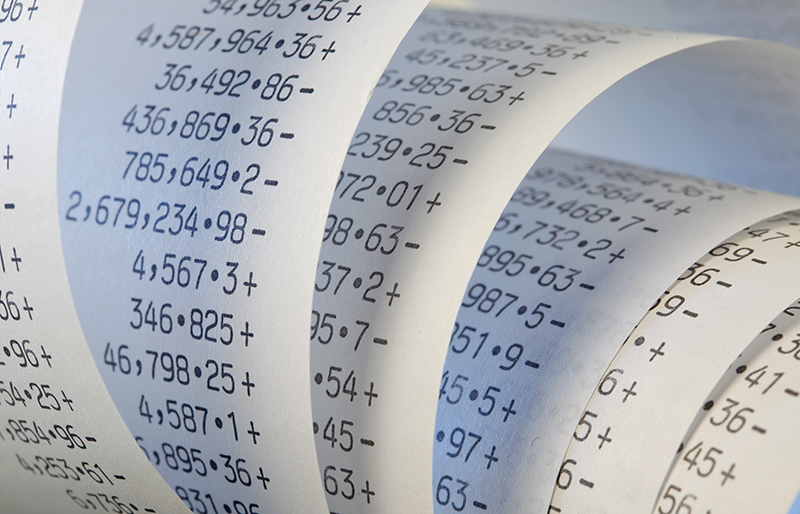Calculator paper tape rolled up full of numbers