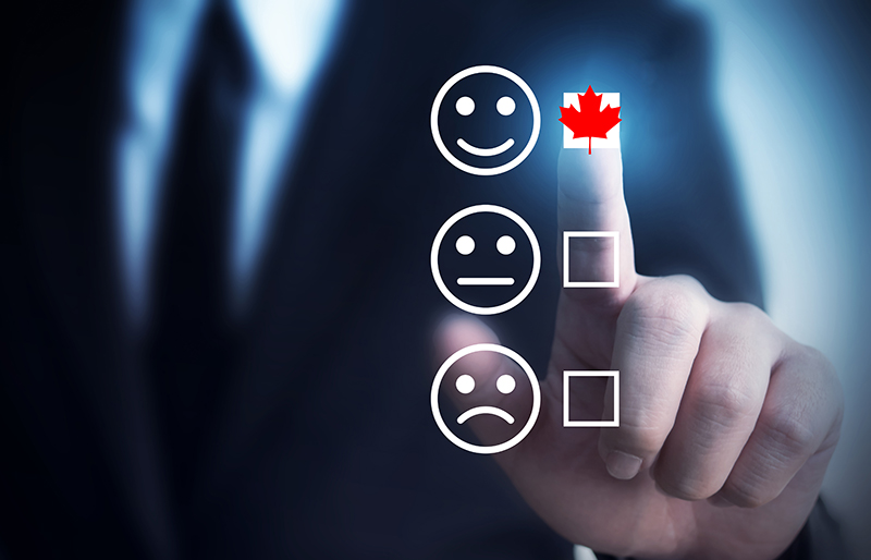 The finger of a business person selecting a box with a Canadian red maple leaf beside a smiley-face icon above a neutral-face icon and sad-face icon with boxes not selected
