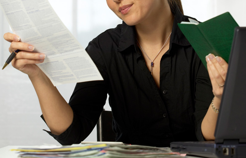 Woman holding invoice in one hand and reference book in the other.