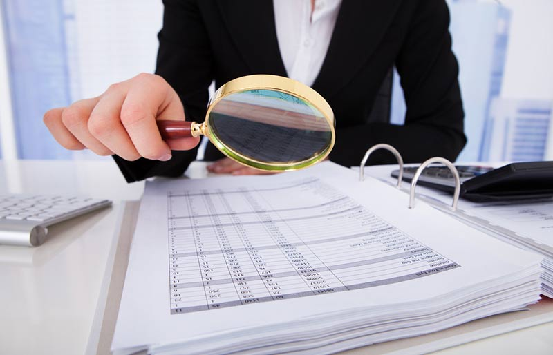 Businesswoman reviewing financial statement with a magnifying glass.