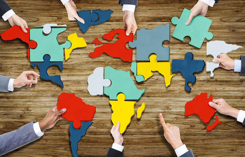 Business people forming world map with puzzle pieces.