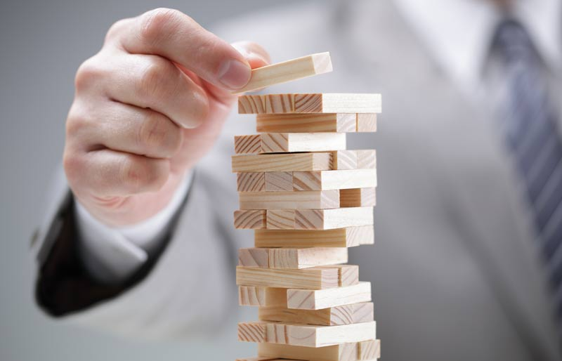 Businessman carefully placing a wooden building block on top of a tower of wooden building blocks.