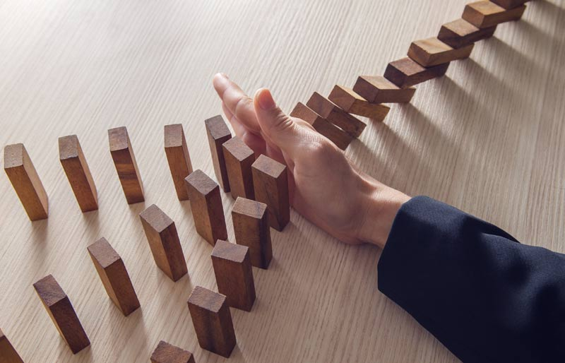 A business woman's hand stopping wooden dominoes from doing a domino effect.