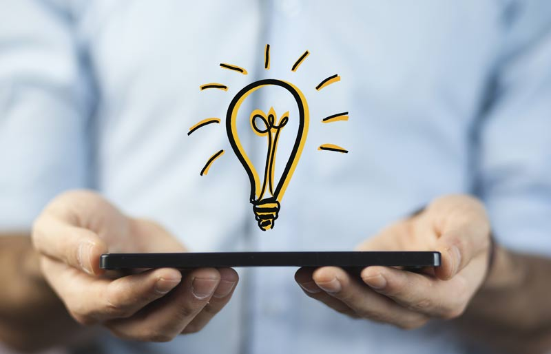 Businessman holding a tablet with a drawing of a light bulb hovering on top.
