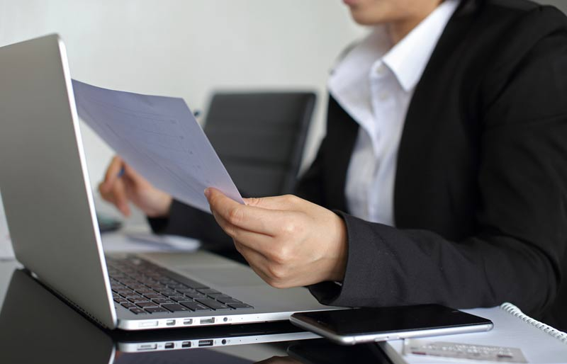 business woman looking at her papers in front of a laptop