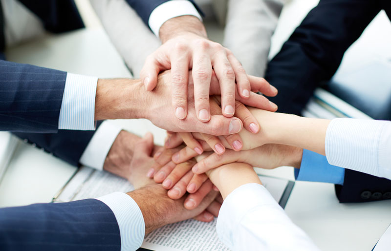 Businessmen and businesswomen perform a hand-over-hand team huddle.