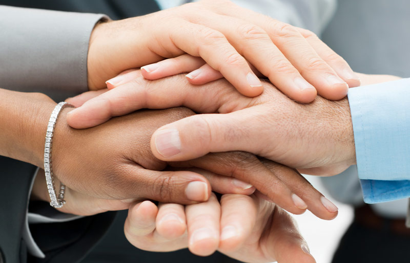 Close-up of businesspeople placing their hands together, one over the other in a form of team huddle.