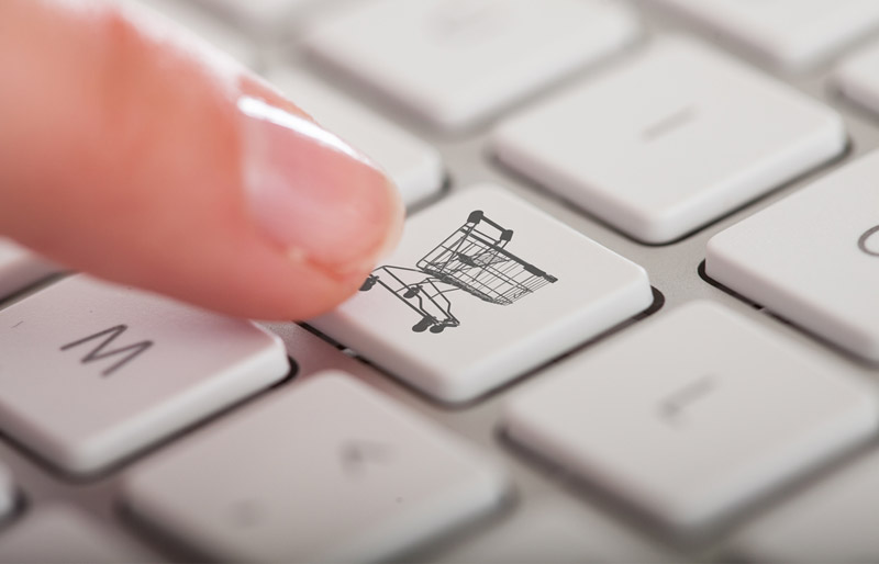 Close-up of a finger pressing a computer keyboard key featuring the image of a shopping basket.