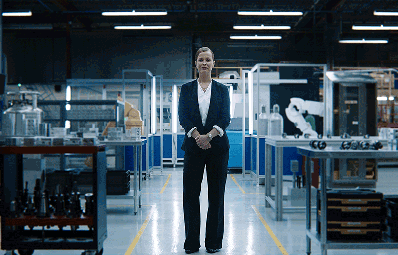 Women standing on forefront of factory floor.